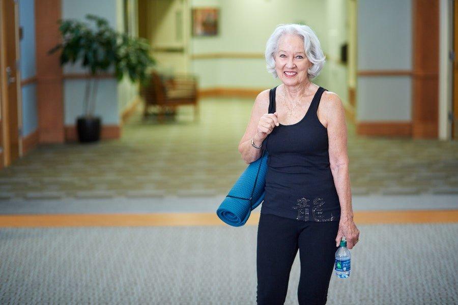 elder woman with a yoga mat