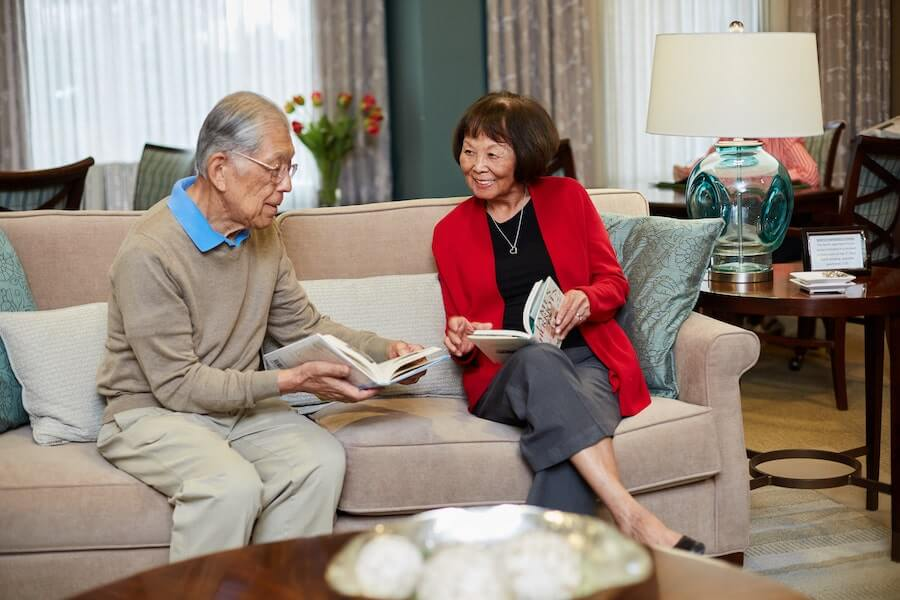 senior couple reading on a couch