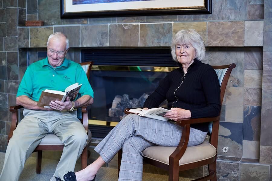 seniors reading next to fireplace