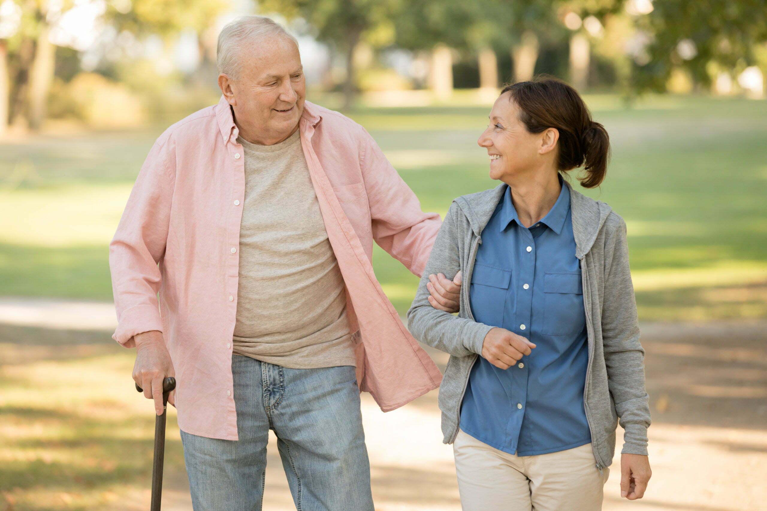 senior resident and caregiver go walking outdoors